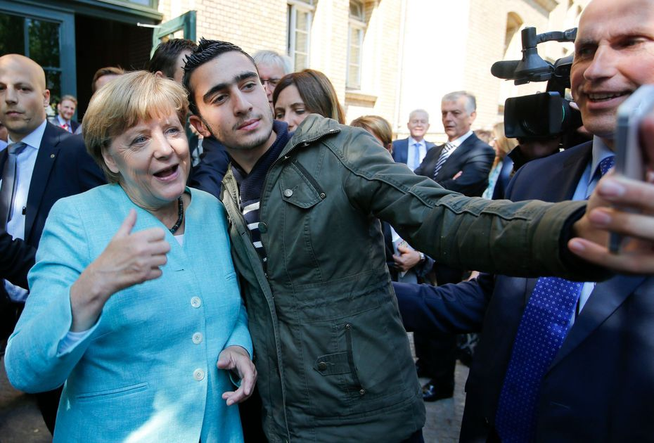 a-migrant-takes-a-selfie-with-german-chancellor-merkel-outside-a-refugee-camp-near-the-federal-office-for-migration-and-refugees-after-registration-at-berlin-s-spandau-district_5413639
