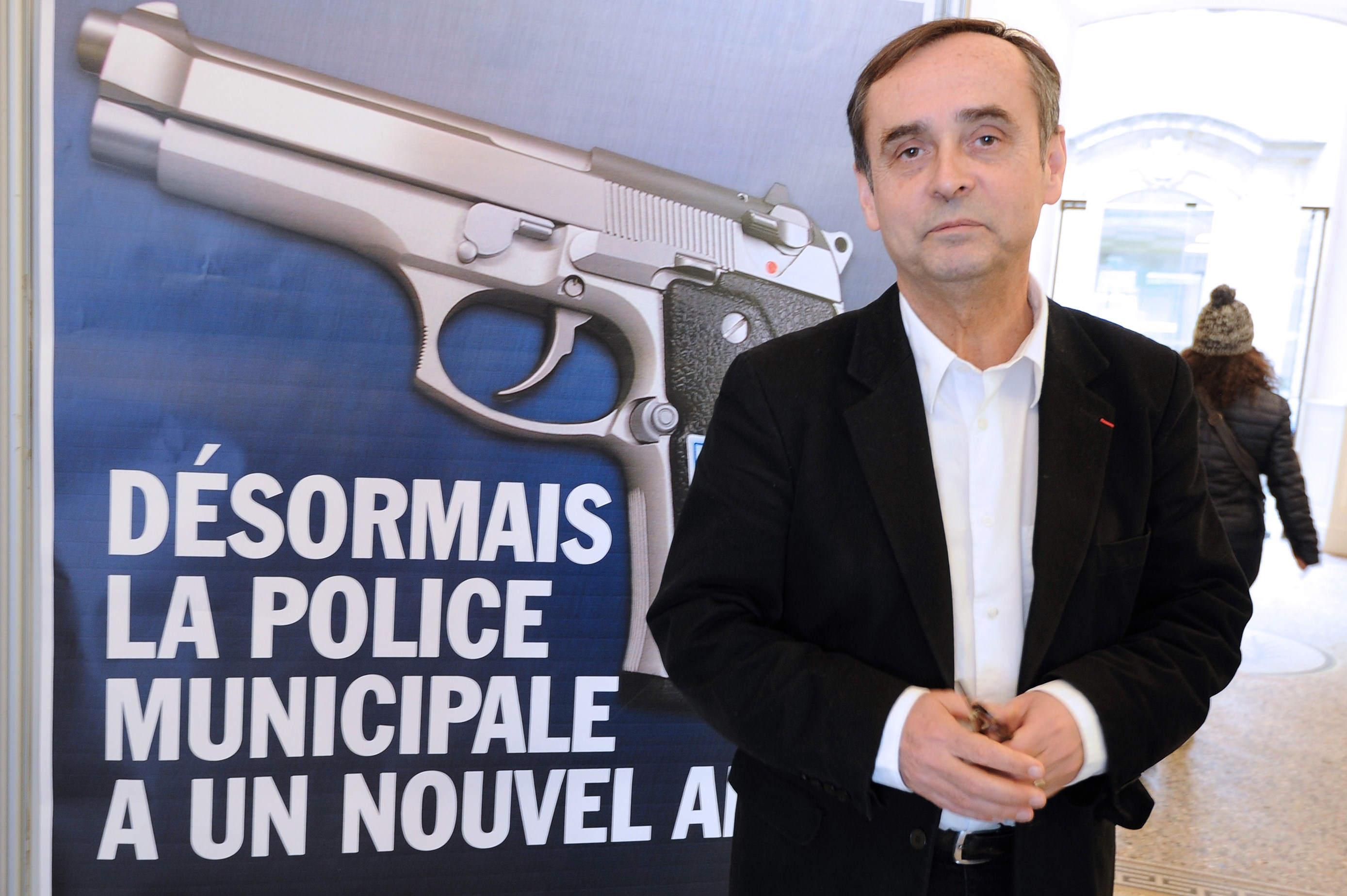 "Beziers mayor Robert Menard poses on February 11, 2015 in front of a municipality campaign poster showing an automatic 7.65 handgun, with a campaign slogans reading : ""From now on, the Municipal Police has a new friend"". Since February 1, the Beziers municipal police is equipped with lethal weapons, in this case automatic 7.65 handguns, as nine armed police officers already patrol the streets, mostly at night, of the town whose far-right party National Front-backed mayor Robert Menard was elected last year. AFP PHOTO / SYLVAIN THOMAS"